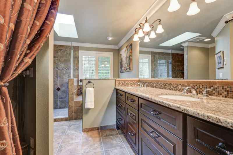 Freshly remodeled bathroom with gorgeous dual sink vanity accented with dark cabinets, granite counters and mosaic backsplash, and skylight over jetted tub and walk-in shower.