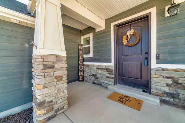 Open porch exterior remodeling home facade with stone wall wood siding and wreath on front door.